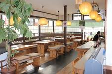 天然木材の大きなテーブルと椅子が並ぶ明るい店内。
