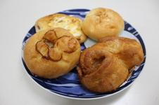 (写真右前から)シナモンロール、ごぼうサラダパン、ベーコンエッグパン、めんたいポテトパン