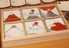 色絵銀彩富士図9cm角小皿シリーズ<br />福珠窯では丁寧に細工された白磁の素地に色絵と銀彩で様々な富士図を表現しています。<br />日の出富士、桜富士、千鳥富士、赤富士、雲上富士など、様々な富士の景色をお楽しみいただけます。