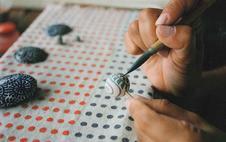 絵付けの様子 (アクセサリーなど小さい物に描きくときは楊枝に差して書きます。)