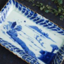 福泉窯 染付山水フリル盛皿<br/>渕がフリル状になった角皿は贅沢でお祝いの席にもぴったりです。